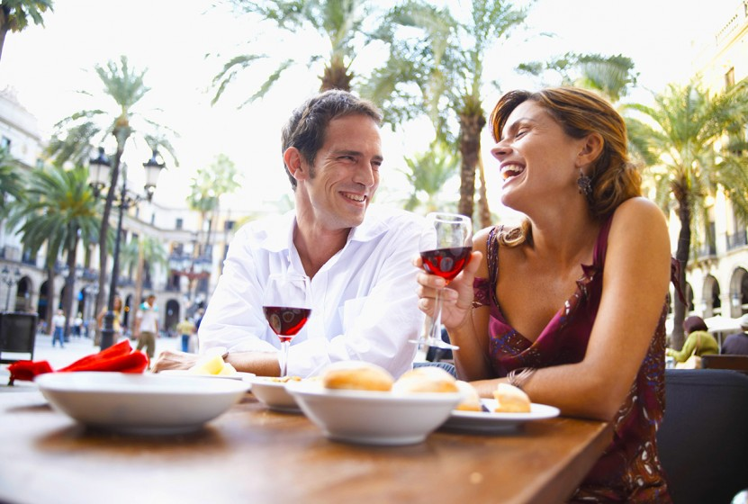 Spain, Barcelona, Placa Real, couple at outdoor cafe, laughing